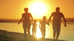 Happy young family running along the beach at sunset summer warm evening - stock footage