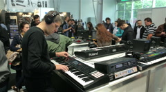Stock Video Footage of Man plays electric piano at the exhibition of musical instruments.