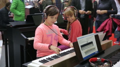 Girl playing the Electric piano at the exhibition of musical instruments. Stock Footage