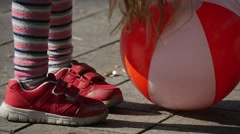 Little Girl With Long Fair Hairs is Playing Ball Legs in Red Sneakers Close Up - stock footage