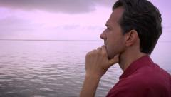 Worried man on beach thinks about his life and contemplates it's meaning Stock Footage