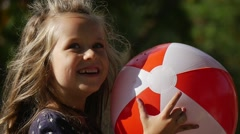 Little Girl Face Close Up With Long Fair Hairs is Playing Ball Holding the Ball - stock footage