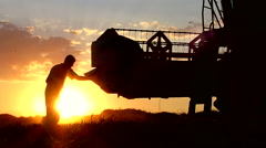Combine header cleaning after wheat harvesting. Summer sunset. Stock Footage