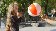 Little Girl With Long Fair Hairs is Playing Ball Throws the Ball to Her Mom - stock footage