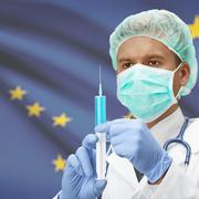 Doctor with syringe in hands and US states flags on background series - Alask Stock Photos