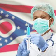 Doctor with syringe in hands and US states flags on background series - Ohio - stock photo