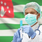 Doctor with syringe in hands and flag on background series - Abkhazia - stock photo