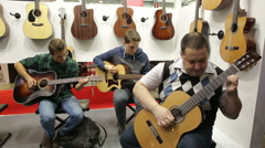 Visitors to the music salon testing new acoustic guitar. Stock Footage