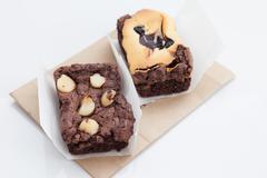 Chocolate brownie with macadamia on white background. Stock Photos