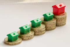 Ascending Row of British Pound Coins and Houses Stock Photos