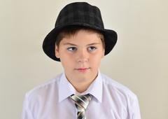 Stock Photo of portrait of a teenage boy in  hat and tie