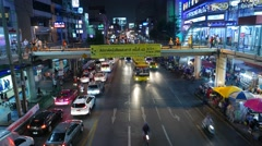 Elevated pedestrian passage over lively night road traffic, people walk Stock Footage