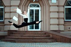 Girl running down the street tossing documents handed. Stock Photos