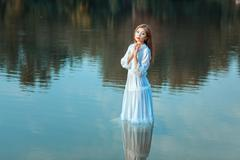 Girl stands in the water. - stock photo