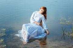 Girl white dress sitting on chair in a lake. - stock photo