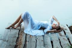 Gentle girl in white dress lying on a wooden pier. - stock photo