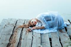 Beautiful girl with sad face lying on a wooden pier. - stock photo