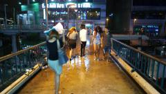 Rainy night, Asian people walk over wet footbridge, above road traffic Stock Footage