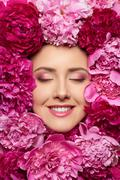 Woman face in peony flowers Stock Photos