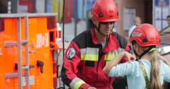 Firefighter is Dressing Child Girl in Helmet Tether Child is Climbing on Rope Stock Footage