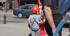 Firefighter is Dressing Child in Helmet and Tether Child is Climbing on Rope Stock Footage