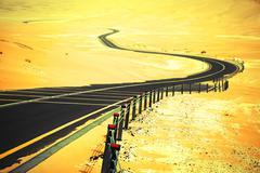 Winding black asphalt road through the sand dunes of Liwa oasis, United Arab  - stock photo