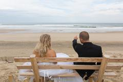 Wedding couple on the bench in front of the sea Stock Photos