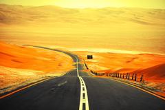 Winding black asphalt road through the sand dunes of Liwa oasis, United Arab  Stock Photos