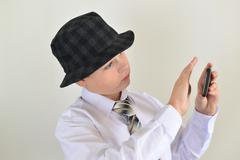Boy teenager turns away from  cell phone - stock photo
