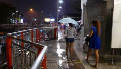 People with umbrella walk at wet elevated passage, night city Stock Footage