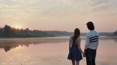 Young couple in love holding hands watching sunrise together outdoors by the lak Stock Footage