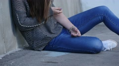 Drug addict girl sits by wall, then falls, dropping syringe. - stock footage