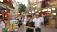 Out of focus people walking though a market Stock Footage