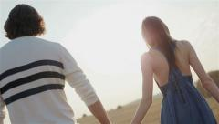 Young couple walking through the field at sunset holding hands. Medium close-up - stock footage