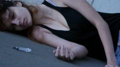 Drug addict girl laying unconscious alone, syringe near, dolly. Stock Footage