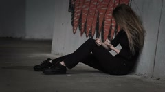 Drug addict girl sits, then falls, dropping syringe, slow motion. Stock Footage