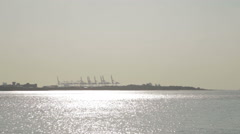 River with gantry cranes silhouette in background Stock Footage