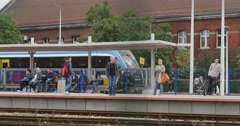 People Stand And Sit On The Benches At The Railroad Station Train Stands At The Stock Footage