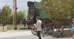 People Are Walking Along Monument of Old Train Locomotive at Railway Station Stock Footage