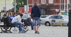 Young Men Are Sitting on A Bench Young Man Smokes Cigarette People Walk Around Stock Footage