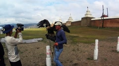 Mongolian provincial TV interviews the owner of an eagle at the walls of the ol Stock Footage