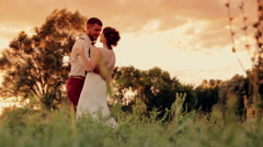 Bride and groom on their wedding day walking outdoors on a spring character Stock Footage