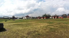 Tourists walk on a green field near several Buddhist temples in the distance Stock Footage