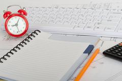 Exercise book and red  alarm clock - stock photo