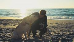 young man with his dog on a beach drinking from thermocup slow motion - stock footage