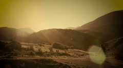 A cowboy riding his horse in the mountains on sunrise Sepia in slow motion Stock Footage