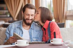 Cheerful young loving couple is dating in cafe Stock Photos