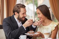 Cheerful young loving couple is dating in restaurant - stock photo