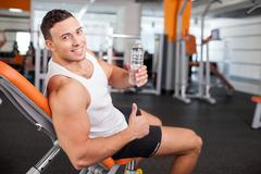 Handsome young male athlete is resting after training - stock photo