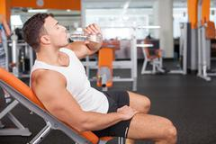 Cheerful young male sportsman is very thirsty Stock Photos
